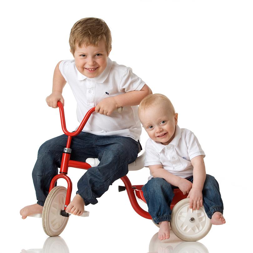 Barn på röd trehjuling