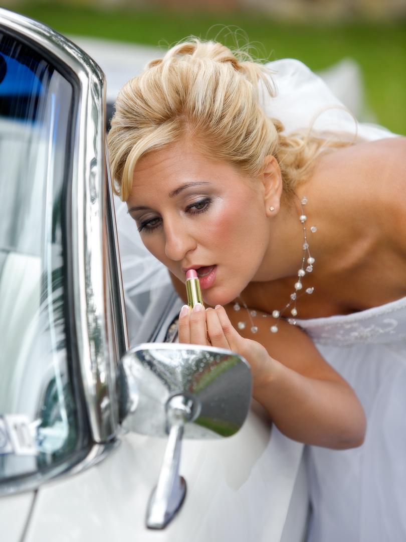 Brud sminkar sig i backspegel